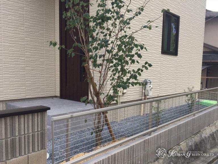 芝のグリーンをバックに映える黒いタイル貼りの門柱 宇治市